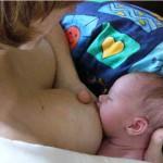 Ein gut angelegtes Baby hat den Mund voll Brust